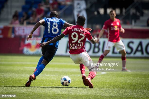 Kemar Lawrence of New York Red Bulls battles for control with Chris Duvall of Montreal Impact during the Major League Soccer match between Montreal...