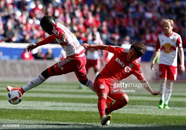 Kemar Lawrence of New York Red Bulls fights for the ball with Tsubasa Endow of Toronto FC during their match at Red Bull Arena on March 6 2016 in...