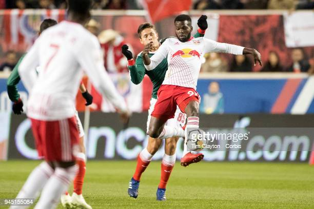 Kemar Lawrence of New York Red Bulls is challenged by Jose Godinez of CD Guadalajara during the New York Red Bulls Vs CD Guadalajara CONCACAF...