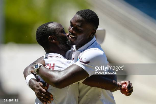Kemar Roach and Jayden Seales of West Indies hug in celebration after dismissing Hasan Ali of Pakistan during day 4 of the 1st Test between West...