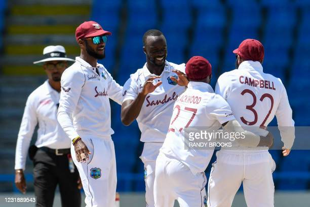 Kemar Roach and Kraigg Brathwaite of West Indies celebrate the dismissal of Dimuth Karunaratne of Sri Lanka during day 3 of the 1st Test between West...