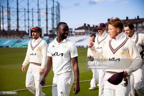 Kemar Roach of Surrey talks to Ollie Pope of Surrey as he leads the team off the field after taking career best figures of 8 for 40 during day three...
