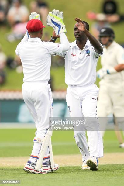 Kemar Roach of the West Indies celebrates with teammate Shane Dowrich of the West Indies after taking the wicket of Jeet Raval of New Zealand during...