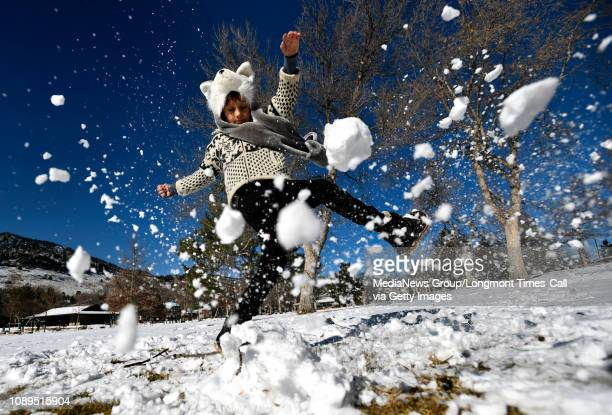 Kemba Click uses his boot to smash the snow dinosaur he built in the warmer weather on Wednesday at the North Boulder Park in Boulder