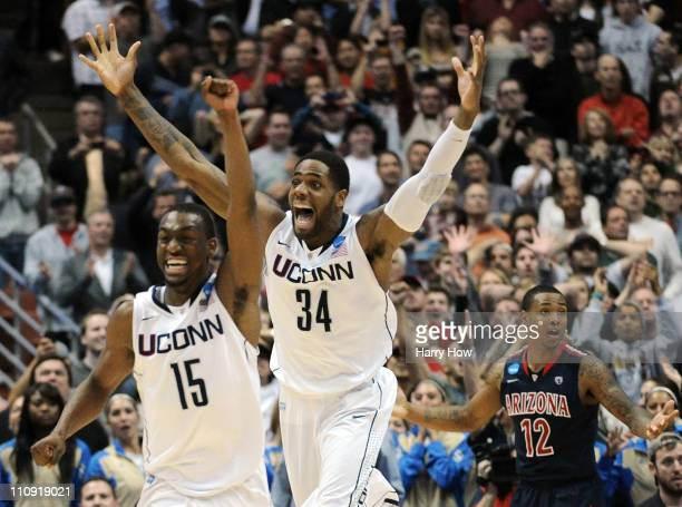 Kemba Walker and Alex Oriakhi of the Connecticut Huskies celebrate after defeating the Arizona Wildcats as Lamont Jones looks on during the west...