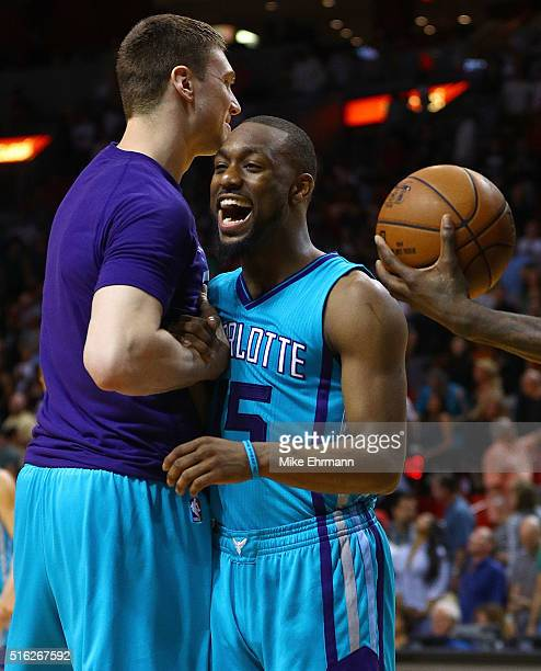 Kemba Walker and Tyler Hansbrough of the Charlotte Hornets celebrate winning a game against the Miami Heat at American Airlines Arena on March 17...