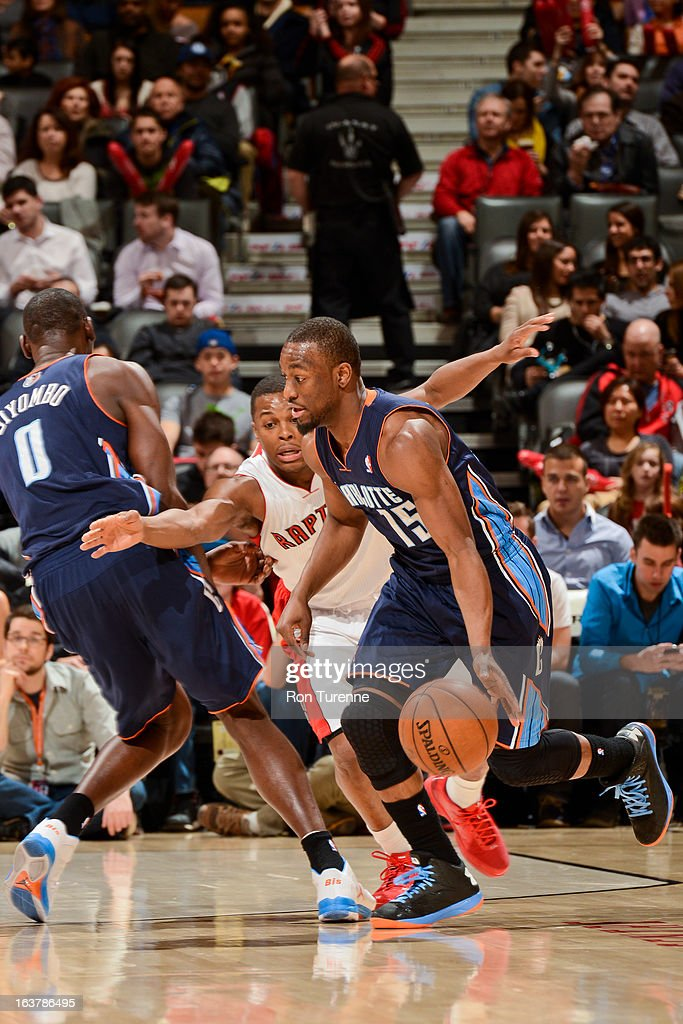 Kemba Walker #15 of the Charlotte Bobcats drives on a screen by teammate Bismack Biyombo #0 against Kyle Lowry #3 of the Toronto Raptors on March 15, 2013 at the Air Canada Centre in Toronto, Ontario, Canada.