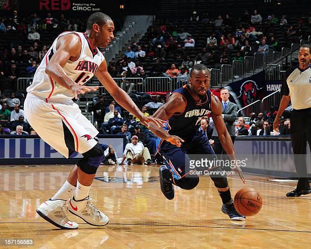 Kemba Walker of the Charlotte Bobcats handles the ball against Al Horford of the Atlanta Hawks at Philips Arena on November 28 2012 in Atlanta...