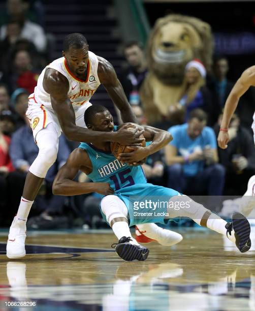 Kemba Walker of the Charlotte Hornets collides with Dewayne Dedmon of the Atlanta Hawks during their game at Spectrum Center on November 28 2018 in...