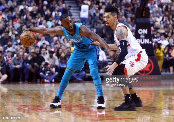 Kemba Walker of the Charlotte Hornets dribbles the ball as Danny Green of the Toronto Raptors defends during the first half of an NBA game at...