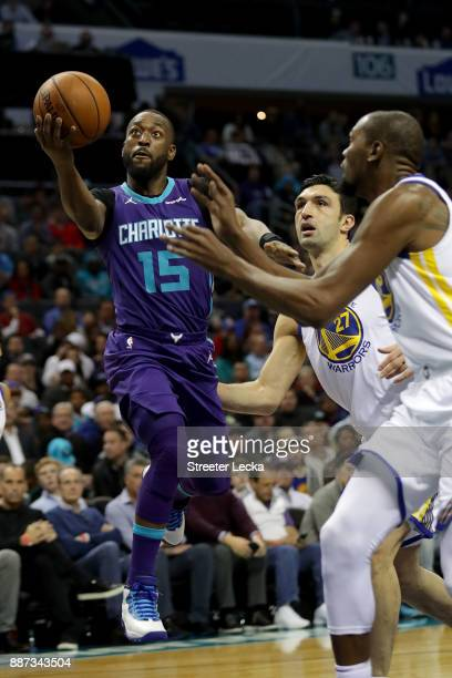 Kemba Walker of the Charlotte Hornets drives to the basket against teammates Zaza Pachulia and Kevin Durant of the Golden State Warriors during their...