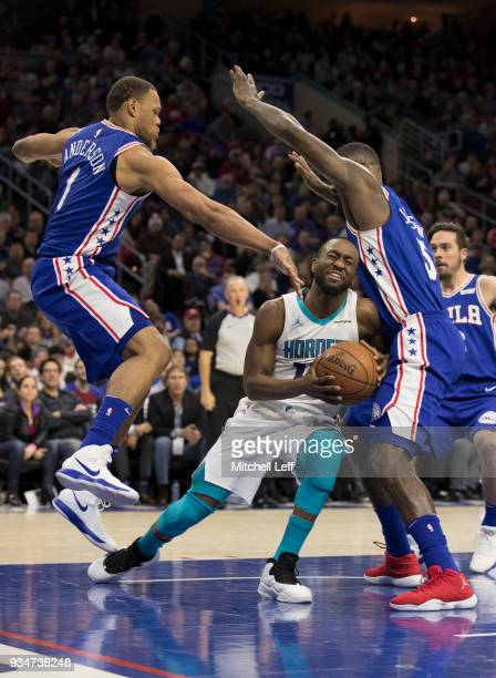 Kemba Walker of the Charlotte Hornets drives to the basket against Justin Anderson and Amir Johnson of the Philadelphia 76ers in the third quarter at...