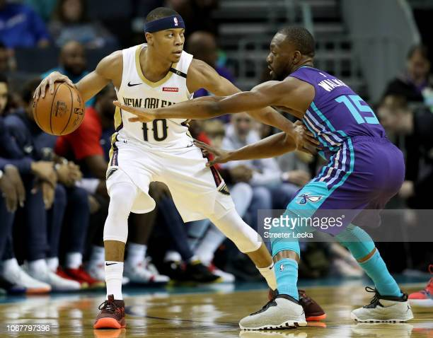 Kemba Walker of the Charlotte Hornets guards Tim Frazier of the New Orleans Pelicans during their game at Spectrum Center on December 2 2018 in...