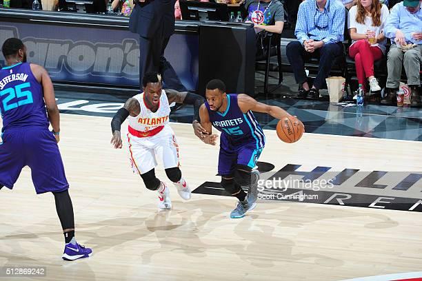 Kemba Walker of the Charlotte Hornets handles the ball against Dennis Schroder of the Atlanta Hawks on February 28 2016 at Philips Center in Atlanta...