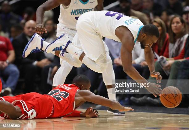 Kemba Walker of the Charlotte Hornets leaps over Kris Dunn of the Chicago Bulls trying to chase a loose ball at the United Center on November 17 2017...