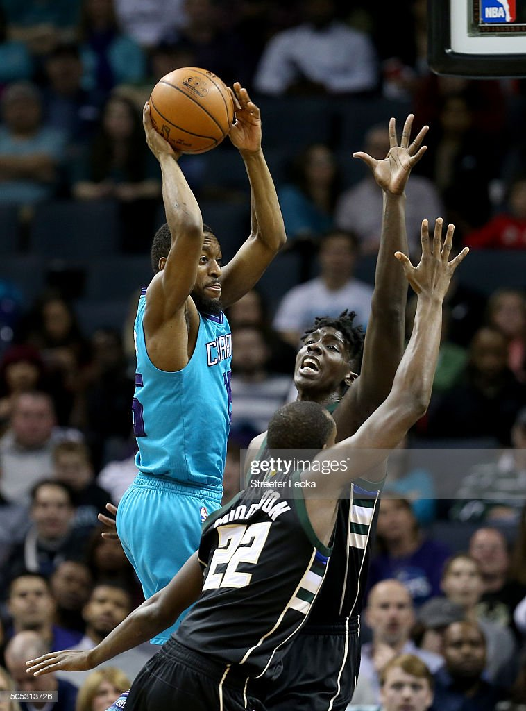 Kemba Walker #15 of the Charlotte Hornets looks to pass over teammates Khris Middleton #22 and Johnny O'Bryant III #77 of the Milwaukee Bucks during their game at Time Warner Cable Arena on January 16, 2016 in Charlotte, North Carolina.