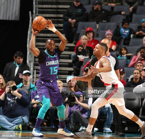 Kemba Walker of the Charlotte Hornets passes the ball against Damian Lillard of the Portland Trail Blazers on December 16 2017 at Spectrum Center in...