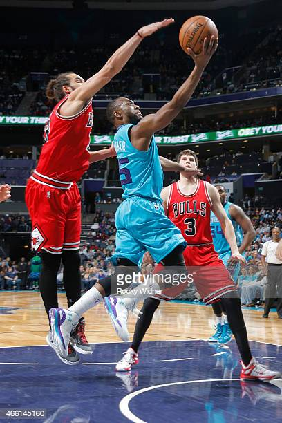 Kemba Walker of the Charlotte Hornets shoots a layup against Joakim Noah of the Chicago Bulls on March 13 2015 at Time Warner Cable Arena in...