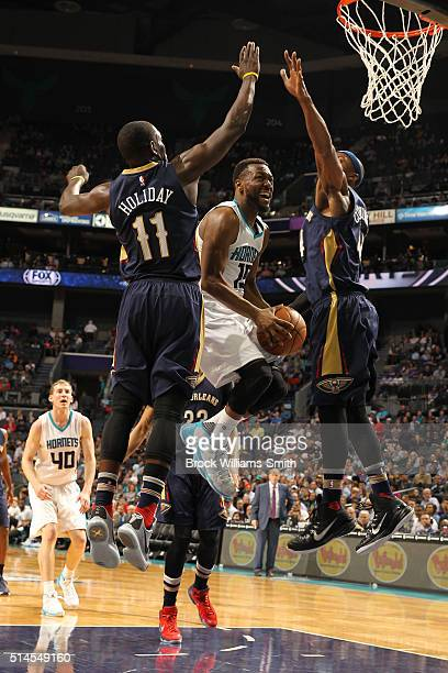 Kemba Walker of the Charlotte Hornets shoots against Jrue Holiday and Dante Cunningham of the New Orleans Pelicans during the game at the Time Warner...