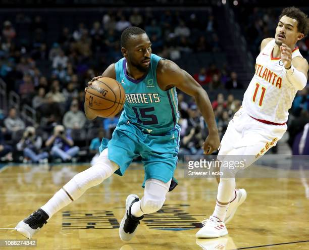 Kemba Walker of the Charlotte Hornets tries to get away from Trae Young of the Atlanta Hawks during their game at Spectrum Center on November 28 2018...