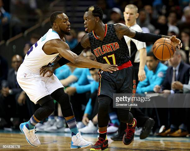 Kemba Walker of the Charlotte Hornets tries to steal the ball from Dennis Schroder of the Atlanta Hawks during their game at Time Warner Cable Arena...