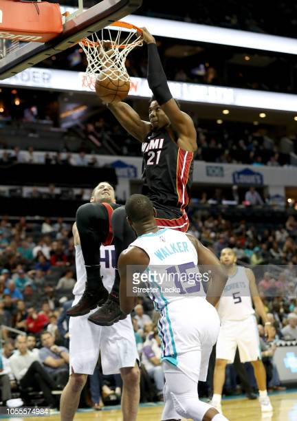 Kemba Walker of the Charlotte Hornets watches as Hassan Whiteside of the Miami Heat dunks the ball during their game at Spectrum Center on October 30...