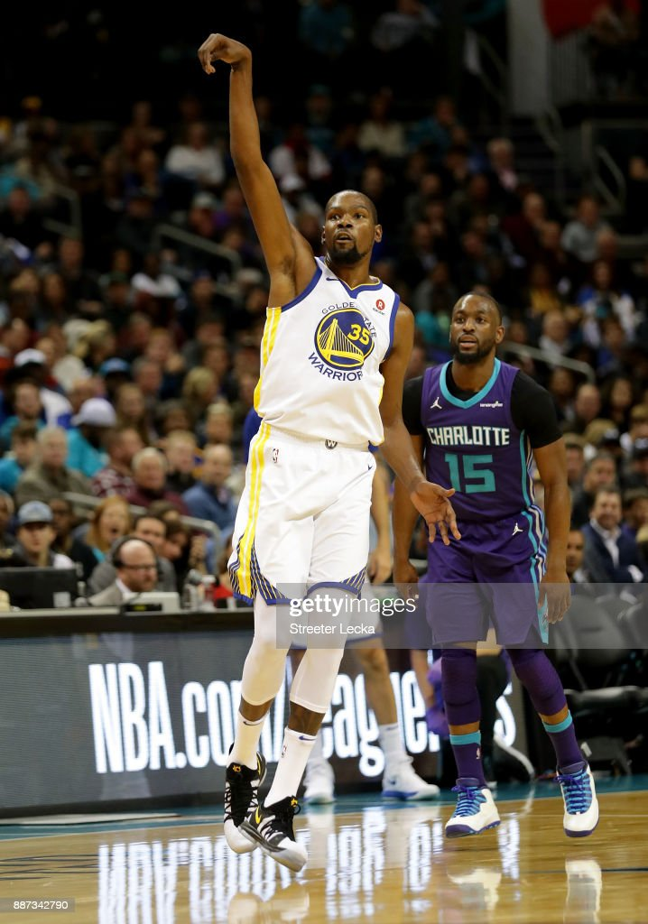 Kemba Walker #15 of the Charlotte Hornets watches as Kevin Durant #35 of the Golden State Warriors reacts after a shot during their game at Spectrum Center on December 6, 2017 in Charlotte, North Carolina.