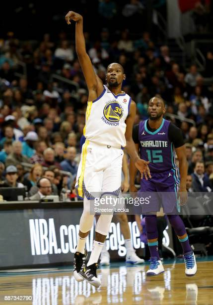 Kemba Walker of the Charlotte Hornets watches as Kevin Durant of the Golden State Warriors reacts after a shot during their game at Spectrum Center...