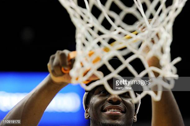 Kemba Walker of the Connecticut Huskies cuts down the net after defeating the Arizona Wildcats during the west regional final of the 2011 NCAA men's...
