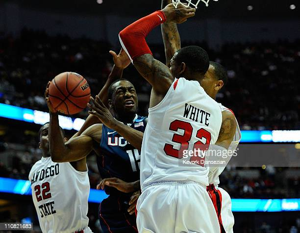 Kemba Walker of the Connecticut Huskies draws contact as he drive to the basket against Chase Tapley and Billy White of the San Diego State Aztecs...
