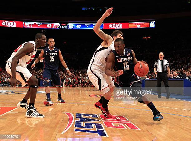 Kemba Walker of the Connecticut Huskies drives with the ball against Mike Marra of the Louisville Cardinals during the championship of the 2011 Big...