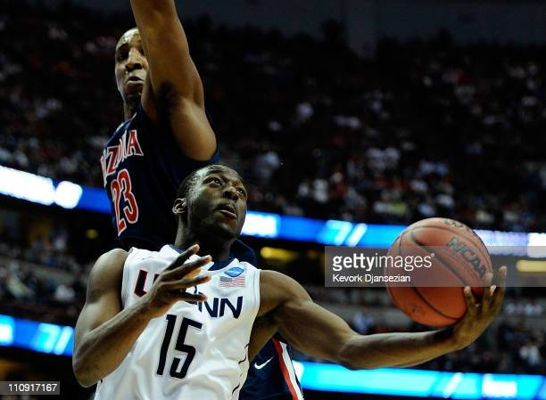 Kemba Walker of the Connecticut Huskies goes to the basket Derrick Williams of the Arizona Wildcats during the west regional final of the 2011 NCAA...