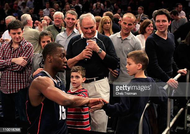 Kemba Walker of the Connecticut Huskies high fives young fans as he walks off the court after defeating the Syracuse Orange during the semifinals of...