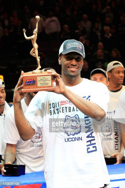 Kemba Walker of the Connecticut Huskies holds up the David R Gavitt Most Outstanding Player trophy after defeating the Louisville Cardinals during...