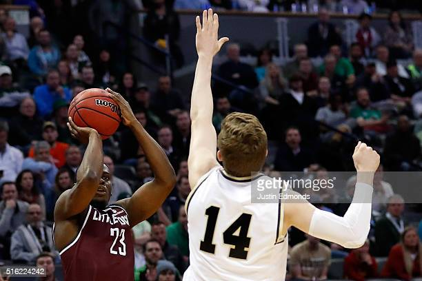 Kemy Osse of the Arkansas Little Rock Trojans makes a three point shot over Ryan Cline of the Purdue Boilermakers in overtime during the first round...