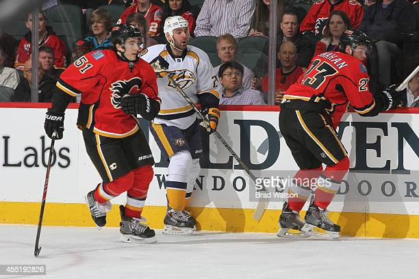 Ken Agostino and Sean Monahan of the Calgary Flames skate against Eric Nystrom of the Nashville Predators at Scotiabank Saddledome on March 21 2014...