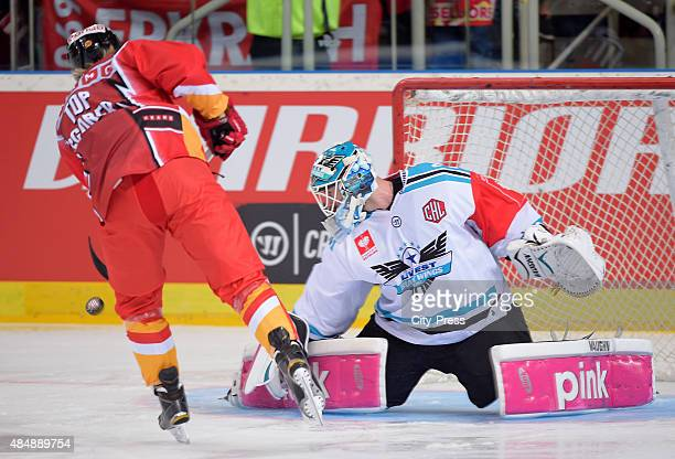 Ken Andre Olimb of the Duesseldorfer EG shoots the puck against Michael Ouzas of the Black Wings Linz during the game between Duesseldorfer EG and...