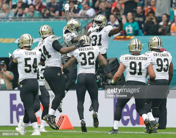 Ken Crawley and Chris Banjo of the New Orleans Saints jump up to celebrate a play in the first half during the NFL game between the Miami Dolphins...