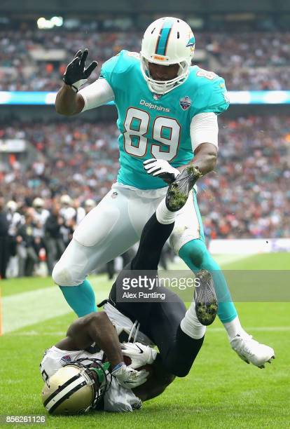 Ken Crawley of New Orleans Saints catches the ball under pressure from Thomas Julius of Miami Dolphins during the NFL International Series match...