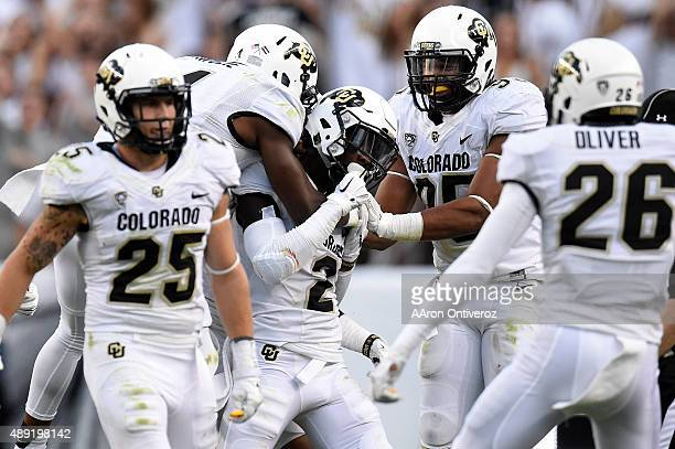 Ken Crawley of the Colorado Buffaloes is swarmed by teammates after making an interception on a ball thrown by Nick Stevens of the Colorado State...