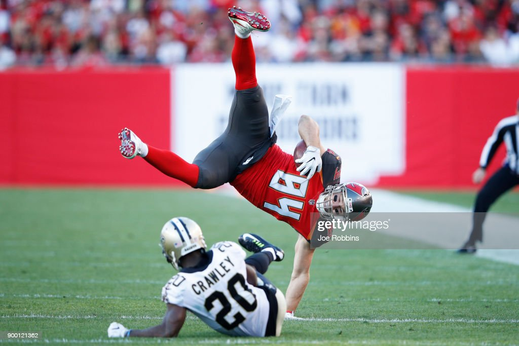 Ken Crawley #20 of the New Orleans Saints trips up Cameron Brate #84 of the Tampa Bay Buccaneers after a catch in the first quarter of a game at Raymond James Stadium on December 31, 2017 in Tampa, Florida.