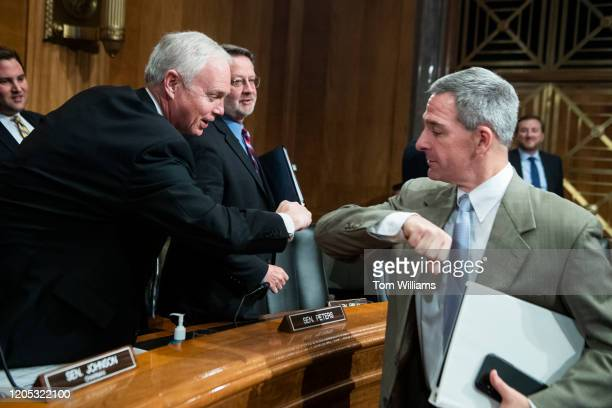 Ken Cuccinelli right acting deputy secretary for the Department of Homeland Security elbow bumps Chairman Ron Johnson RWis to avoid shaking hands due...