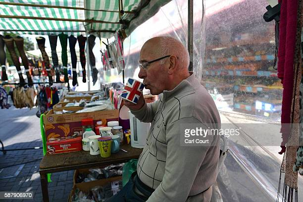 Ken Denton a stall holder for 46 years takes a sip of tea as he waits for customers in Walthamstow market on August 9 2016 in London England...