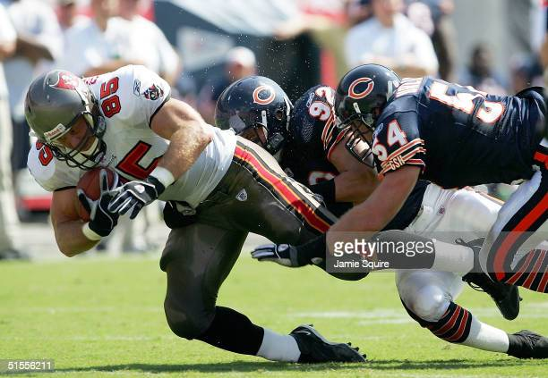 Ken Dilger of the Tampa Bay Buccaneers lunges for an extra yard as Hunter Hillenmeyer and Brian Urlacher of the Chicago Bears tackle during the first...