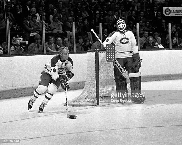 Ken Dryden watches teammate Henri Richard of the Montreal Canadiens skate from behind the net during a game at the Montreal Forum circa 1972 in...