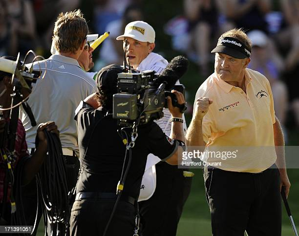 Ken Duke pumps his fist into the TV camera after making the winning putt against Chris Stroud in their second sudden death playoff in the Travelers...