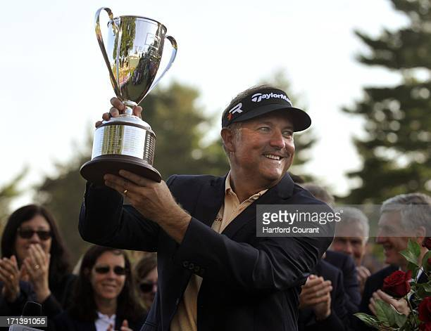 Ken Duke raises the Travelers Championship trophy after beating Chris Stroud on the second playoff hole at the TPC River Highlands in Cromwell...