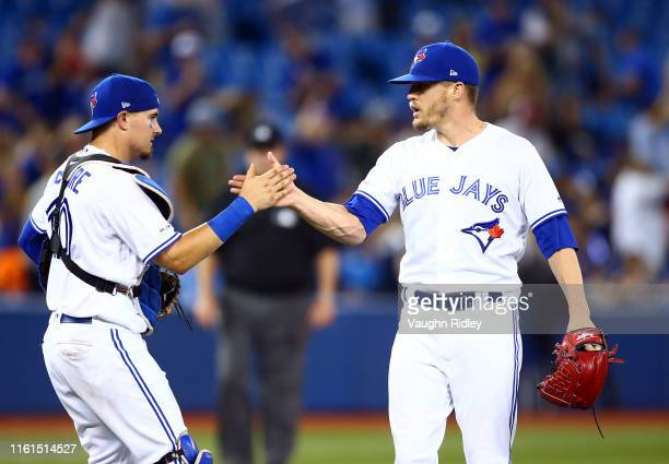 Ken Giles of the Toronto Blue Jays celebrates with Reese McGuire after the final out in a MLB game against the Texas Rangers at Rogers Centre on...