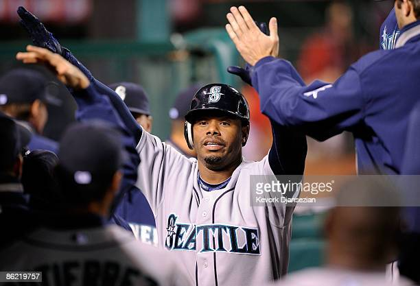 Ken Griffey Jr #24 of the Seattle Mariners is congratulated in the dugout after scoring on a base hit by Russell Branyan against the Los Angeles...
