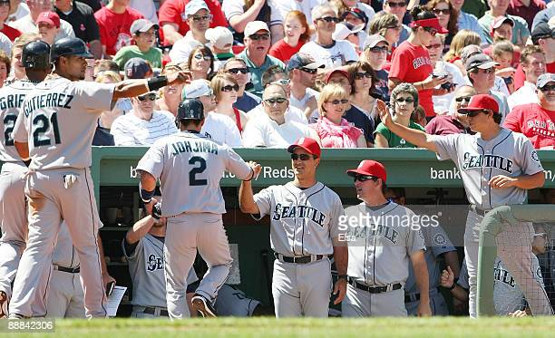 Ken Griffey Jr Franklin Gutierrez and Kenji Johjima of the Seattle Mariners are congratulated by teammates in the dugout after scoring in the fourth...